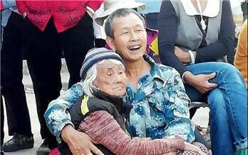丽江男子抱80岁瘫痪老母亲看戏 这画面太暖!太温情!